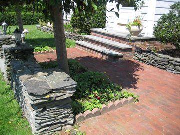 Quaint brick walkways with fieldstone walls at entryway.