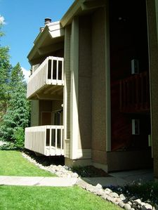Front exterior, summer—condo is 2 levels starting on second floor. View of deck.