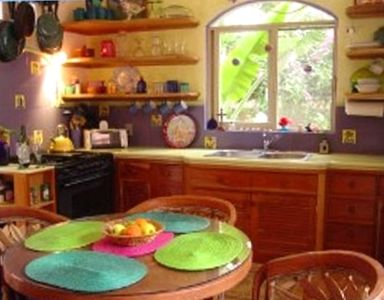 The cheery kitchen has all amenities, dishes, and utensils