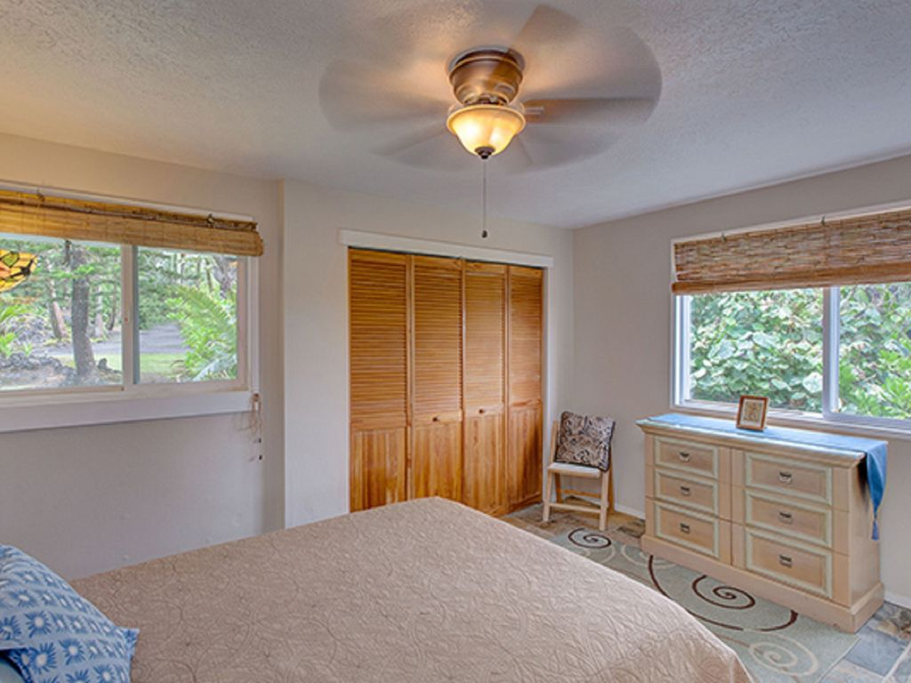 Queen size bedroom with windows and views