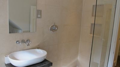 Large walk in shower faces free standing tub