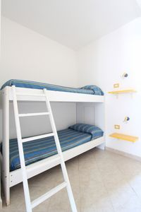 THE BUNK BED WITH BEDSIDE TABLES AND LIGHTS.