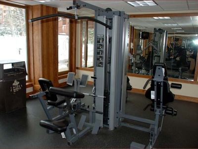 Small fitness center with machines and free weights available to all guests.