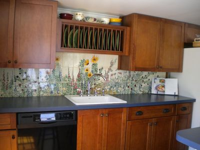 Hand-painted tiles grace the fully-stocked kitchen.