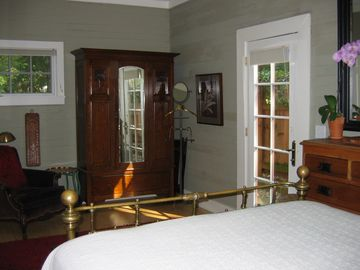 The bedroom is appointed with an antique brass bed, armoire & comfy chair.