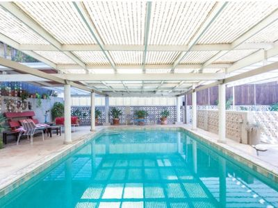 a  solar heated covered pool w/ multiple sitting areas