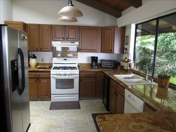 Experience our Upgraded Kitchen with Granite, Tile, & Views to Garden and Pool