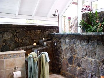Upstairs bathroom has living orchid garden, jacuzzi tub, and natural rock shower