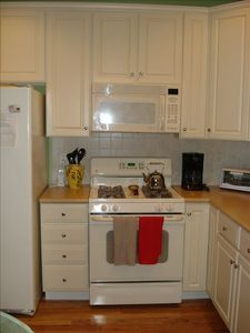 Full L-shaped kitchen with gas oven, microwave, dishwasher & side-by-side fridge