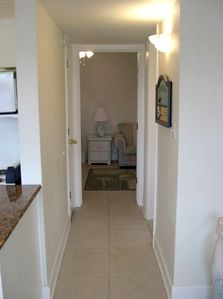 Hallway to large bedroom with queen bed and fold-out love seat. Bath is on right