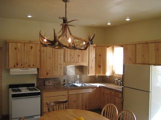 Guffey farmhouse photo - Ranch house kitchen with aspen wood cabinets and elk antler chandelier