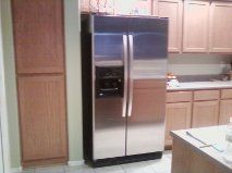 Side by Side Stainless Steel Refrigerator in well stocked kitchen