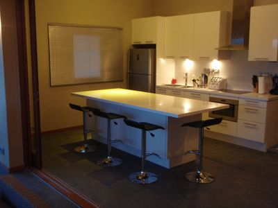 Massive kitchen island/dining table with stone top & barstools