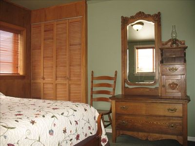 Upstairs bedrooms with full size bed, antique dresser & green wing back chair
