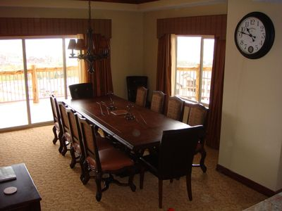 Dining room table w/balcony beyond; can seat 12, game table seats 4, 4 barstools