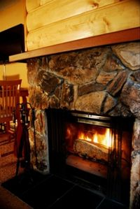 Wood burning fireplace with a lodge feel makes for a cozy living room