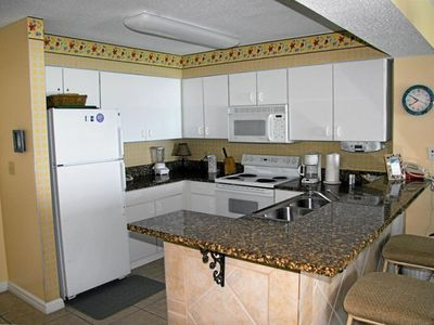 Granite countertops in fully equipped kitchen.