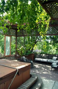 Pergola-covered  hot tub and shaded seating area