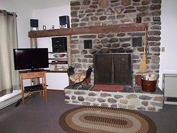 Stone wood fireplace with TV w/ DVD & VCR in main living room