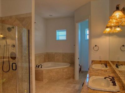 Bath in detached Master with Jacuzzi corner tub, shower, and double vanity sink.