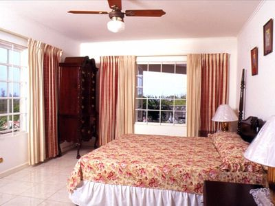 Master bedroom w/ private bath & view  of pool and sea