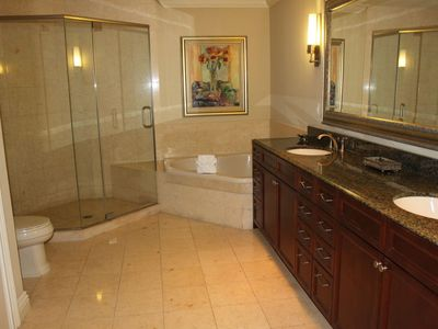 Luxurious bath with oversized shower and garden tub. Large double-sinked vanity