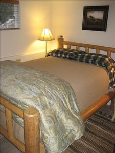 Bedroom 3 has a standard size log bed and Western decor