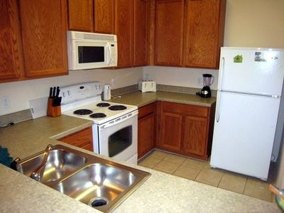Fully-equipped kitchen with stove, refrigerator, microwave, and dishwasher.