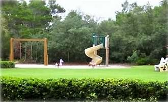 View of playground between tennis courts and pool area