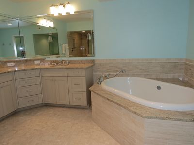Master bath with tub and granite counters