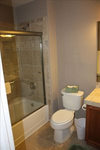 Hall bath with tile shower and glass doors. Towels provided.