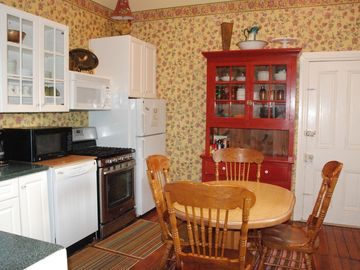 Sunny eat-in kitchen with gas stove, microwave and other appliances.