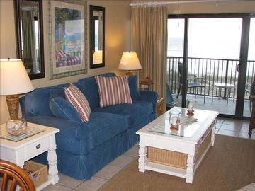 Ponce Inlet condo rental - View from Dining room into Family room with new couch, and oceanfront balcony..