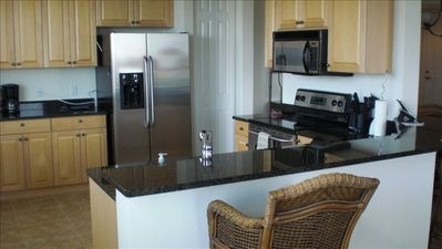 Kitchen with stainless appliances, large cooking area with breakfast bar.