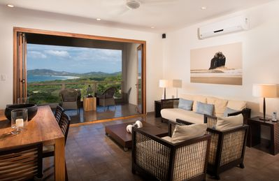 Open Doors - A great shot of the living room with the bi-folding doors open so you can enjoy the cool, tropical breeze!