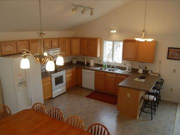 Open fully-stocked kitchen with vaulted ceilings and table for family gathering