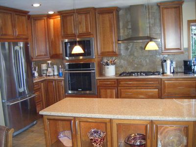 Kitchen with granite counters, and all new cherry wood cabinets.
