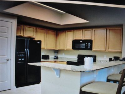 Kitchen with granite counter tops and food pantry. Completely furnished.