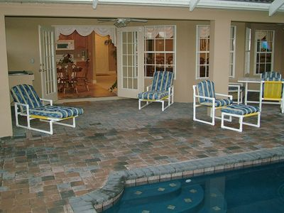 Shady lanai next to a relaxing pool. The area has an electric BBQ & large table.