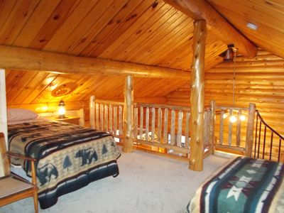 There are 4 beds in the loft. This is a view of the loft towards the log railing