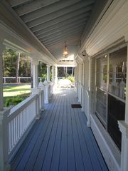 Naples house photo - 55 ft. front porch with casual southern white whicker seating at each end