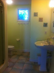 Modern bathroom with storage.  1 roll of toilet paper and hand soap supplied,