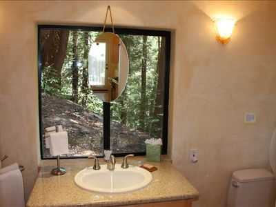 Pristine bathroom with granite and art glass lighting.