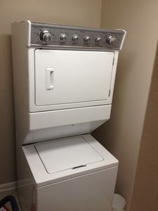 New washer and dryer in utility room with iron and ironing board