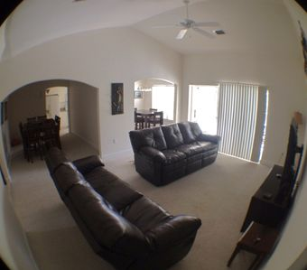 living room with carpet, door to lanai, archway to kitchen, and to dining area
