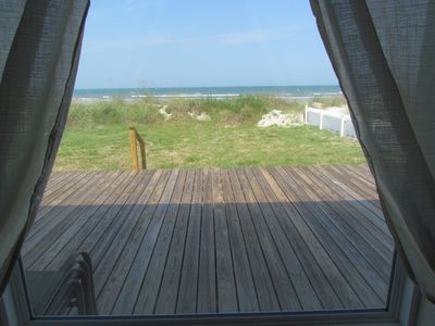 View of the ocean, deck, and backyard