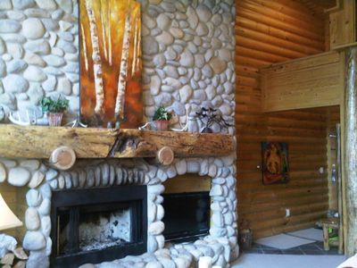 River rock fireplace with log mantel and original art accents