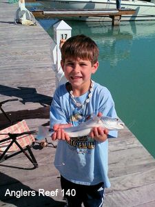 A happy little angler with his redfish from the Anglers boat lagoon.