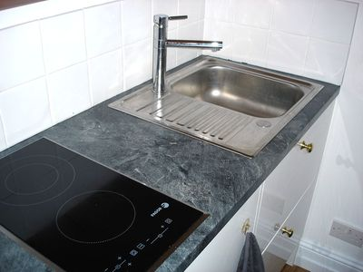 CERAMIC HOB with fridge and stainless steel sink. Abundant cupboard space.