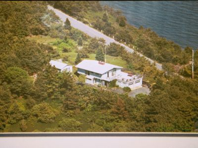 Bird's eye view: house+huge deck, cottage (rear), pvt. bay beach below trees rt.